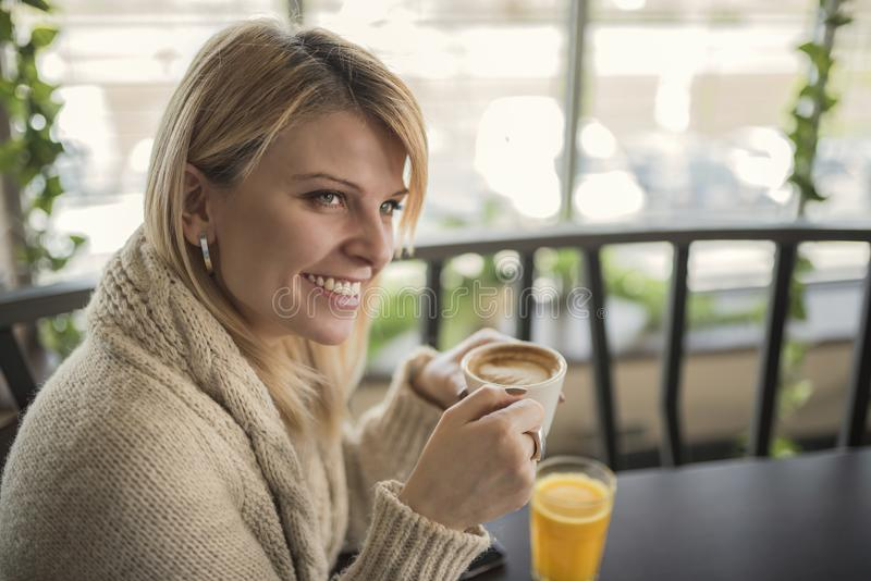 Portrait of young gorgeous female drinking cup of coffee and enjoying her leisure time alone royalty free stock photography