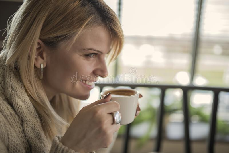 Portrait of young gorgeous female drinking cup of coffee and enjoying her leisure time alone stock photography