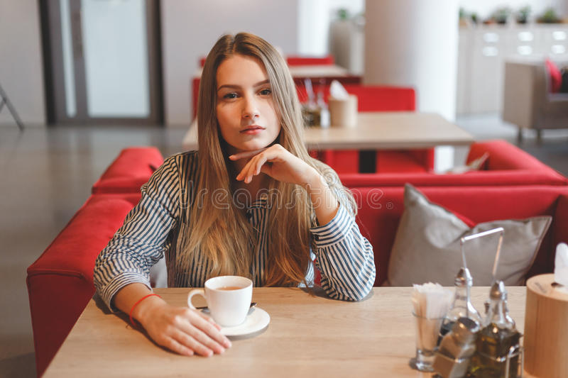 Portrait of young gorgeous girl drinking tea and thoughtfully looking to you while enjoying her leisure time alone. stock photo