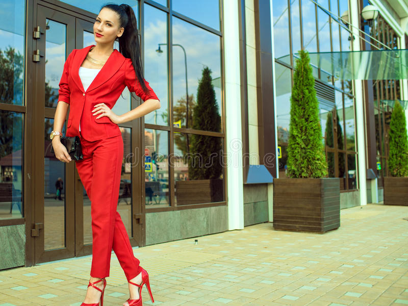 Portrait of young gorgeous lady with high pony tail in red costume and high-heeled shoes in front of mirrored shop windows royalty free stock images