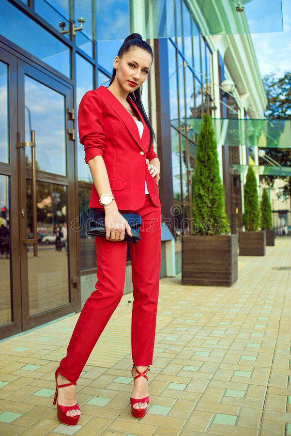 Portrait of young gorgeous lady with high pony tail in red costume and high-heeled shoes standing in front of mirrored shop window stock photography