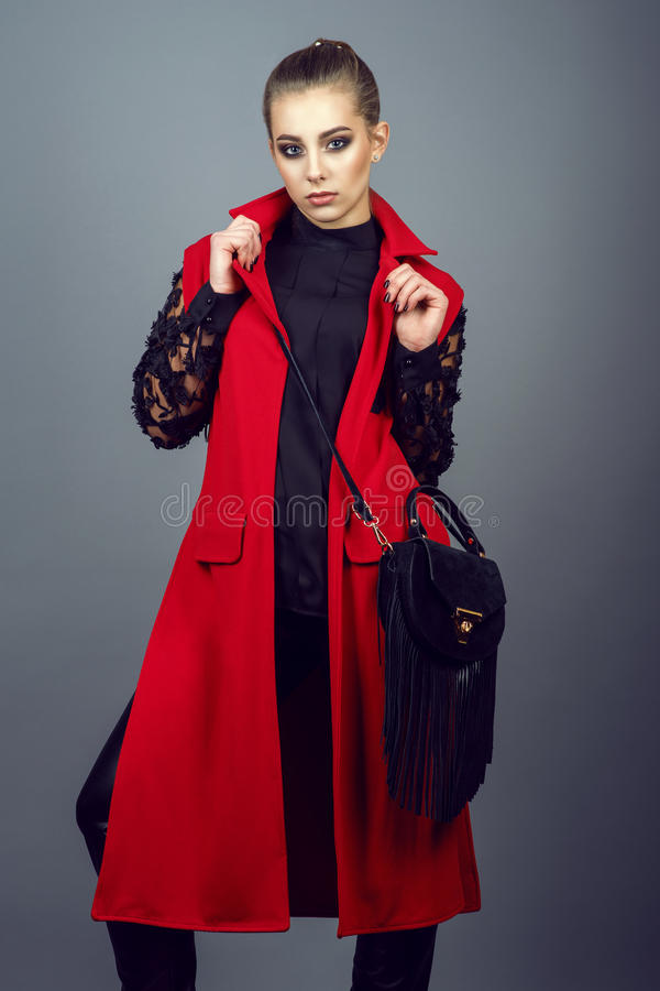 Portrait of young gorgeous model with ponytail and artistic make-up wearing leather pants, black blouse and sleeveless jacket. Portrait of young gorgeous model royalty free stock photos