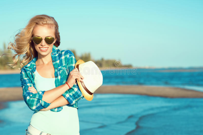 Portrait of young gorgeous suntanned blond wearing mirrored heart shaped sunglasses and checked blue shirt at the seaside stock image