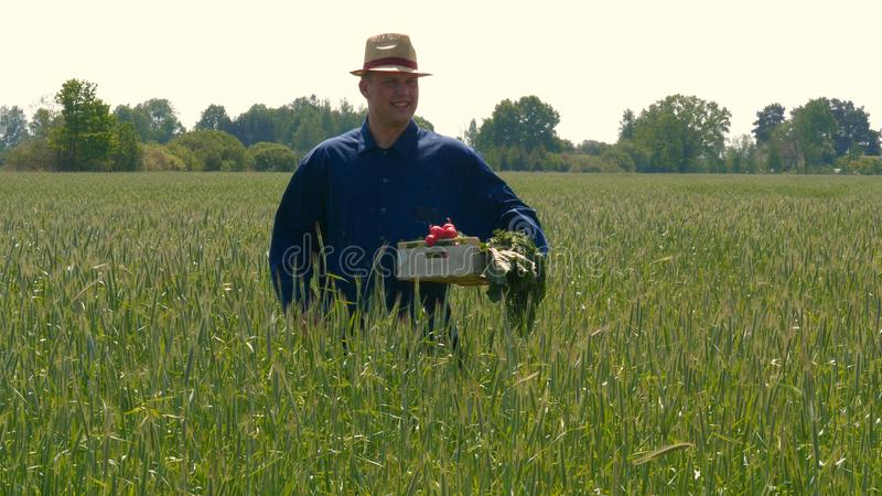 Portrait of a young guy man in a working uniform and a straw hat in the middle of a field around wheat and hay, running around i stock photography