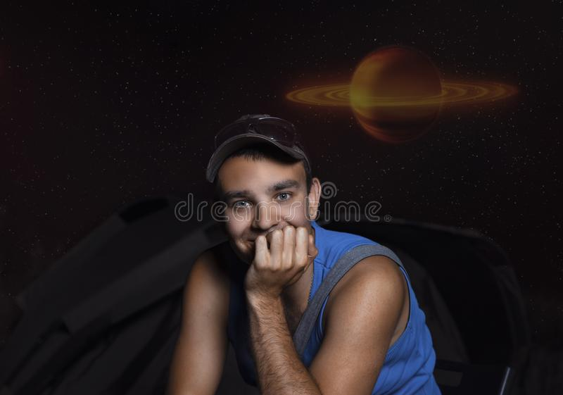 Portrait of a young guy at night on a campsite on a background of stars and a red-yellow planet, abstract image stock photos