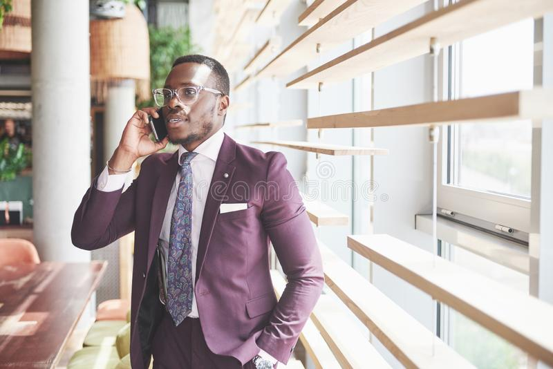 Portrait of a young and handsome African American businessman talking in a suit over the phone royalty free stock images