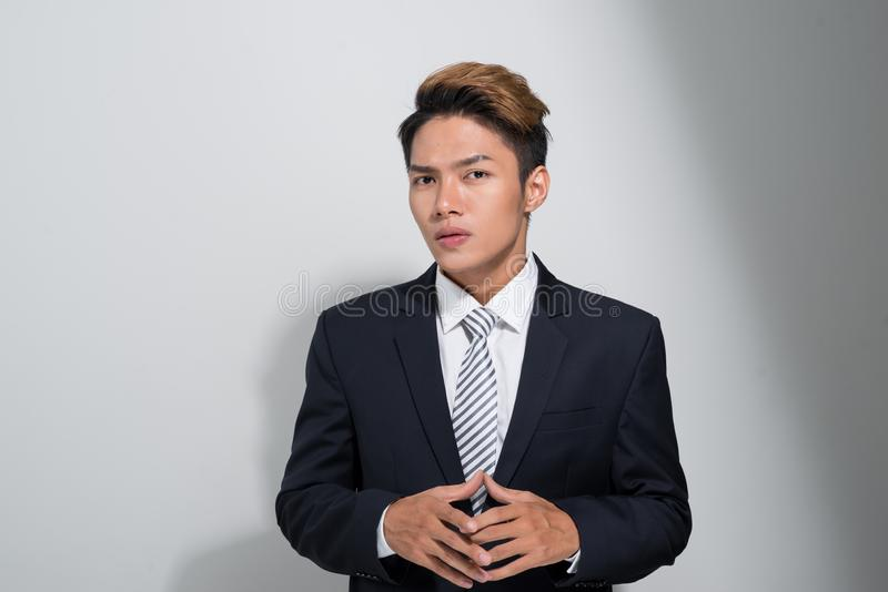 Portrait of young and handsome  Asian business man holding a jacket isolated on white background stock photography