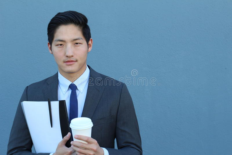 Portrait of a young handsome Asian man businessman in black classic suit with trendy blue tie. Close up of a coffee break stock photography