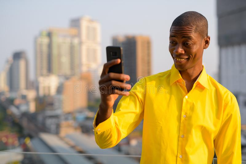 Happy young bald African businessman taking selfie against view of the city stock photo