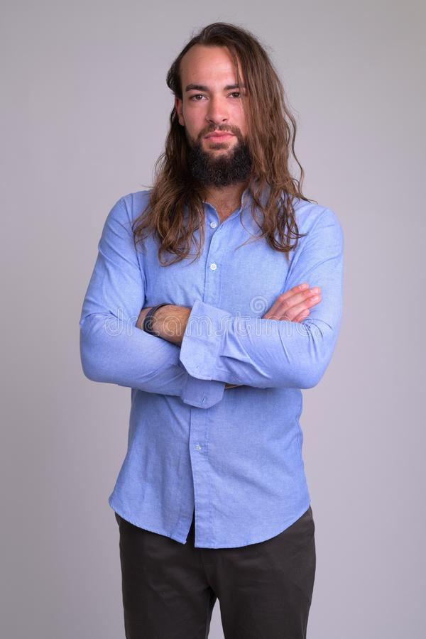 Portrait of young handsome bearded businessman with arms crossed stock photo