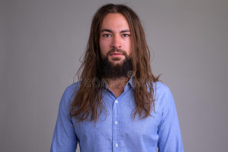 Portrait of young handsome bearded businessman with long hair stock photos