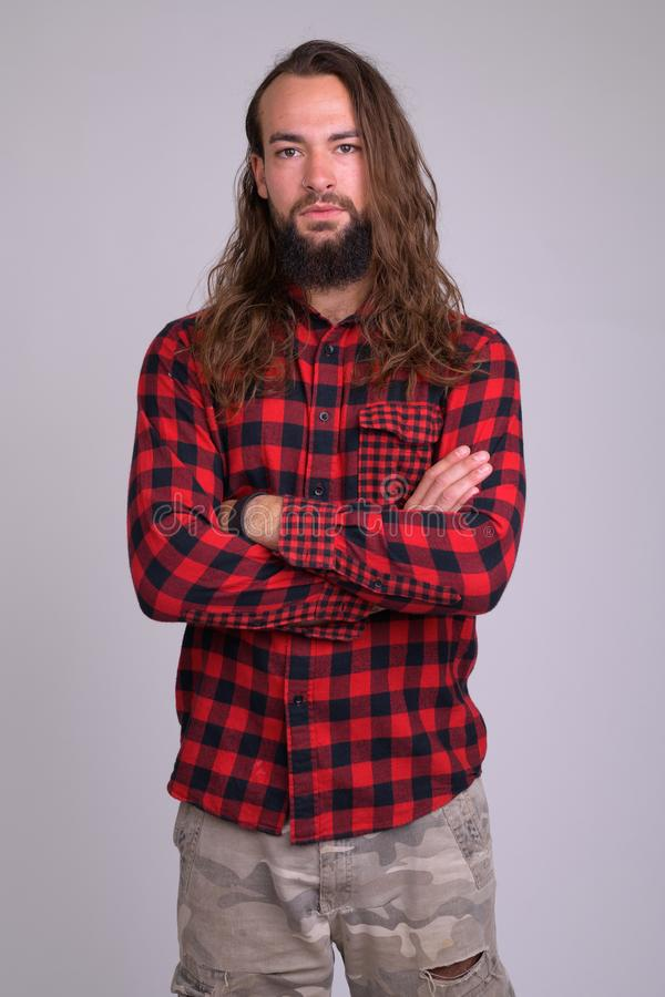 Portrait of young handsome bearded hipster man with arms crossed stock photography
