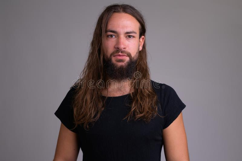 Portrait of young handsome bearded man with long hair stock images