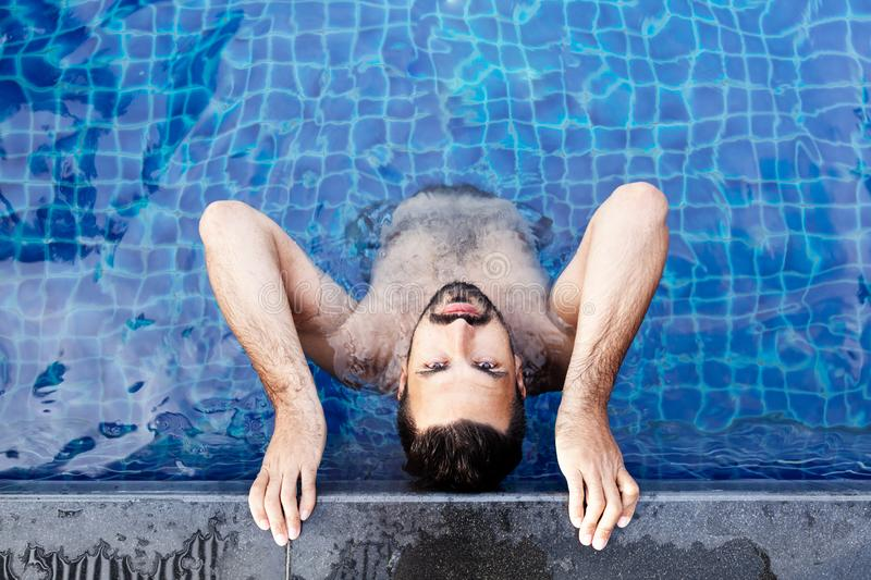 Portrait of a young handsome brutal latin man in an outdoor pool. Attractive guy with a beard stock photography