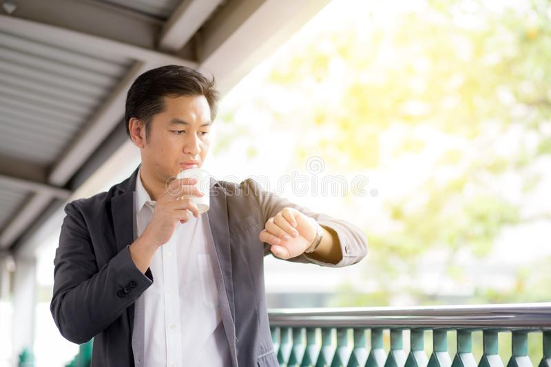 Portrait of young handsome business man drinking coffee looking at wrist watch royalty free stock photo