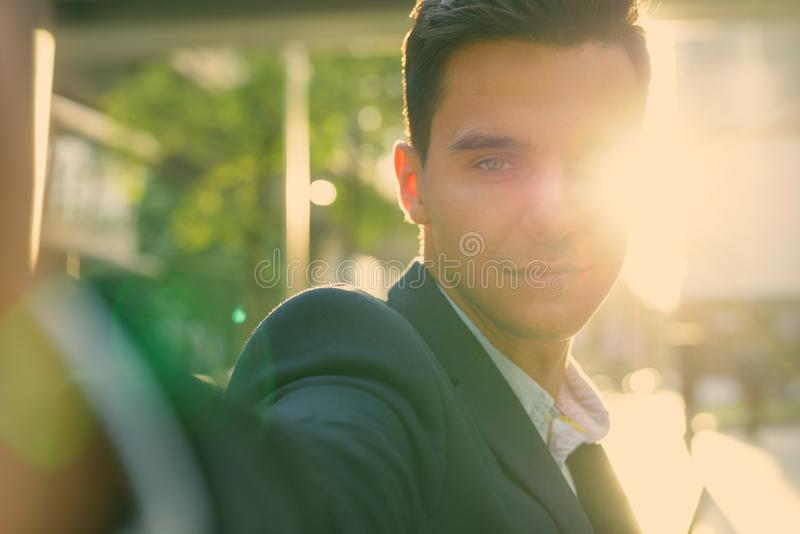 Portrait of young handsome businessman exploring the city stock photo