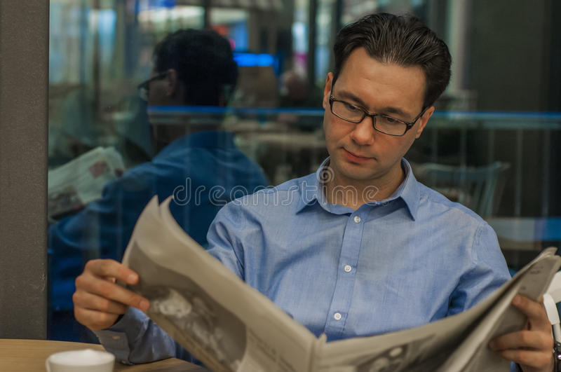 Portrait of a young handsome businessman reading a newspaper at his breakfast in coffee shop. Brunette business man holding open newspaper sitting in cafe royalty free stock images