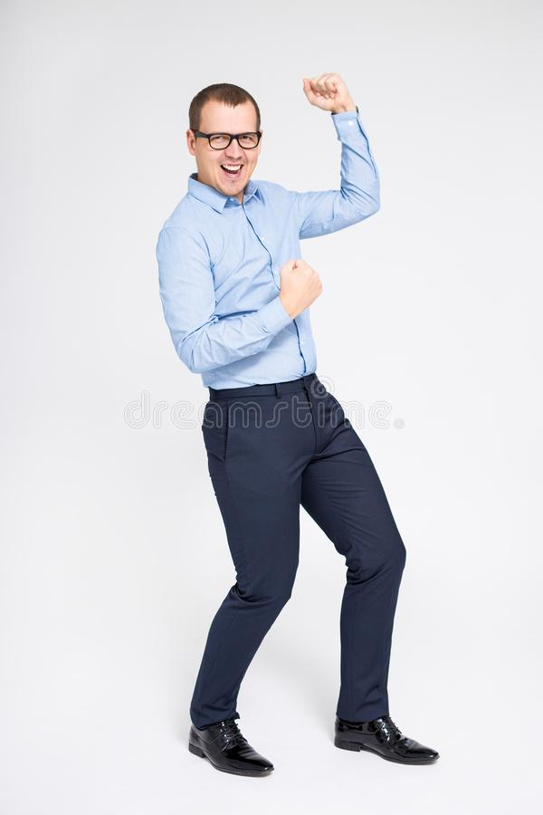 Portrait of young handsome cheerful businessman celebrating something and dancing over gray background royalty free stock photos