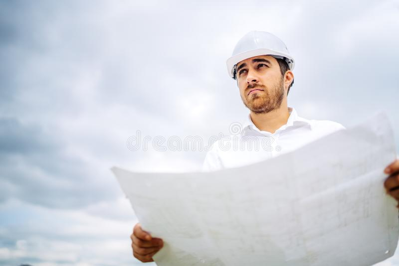 Portrait of handsome civil construction engineer working on construction site stock image