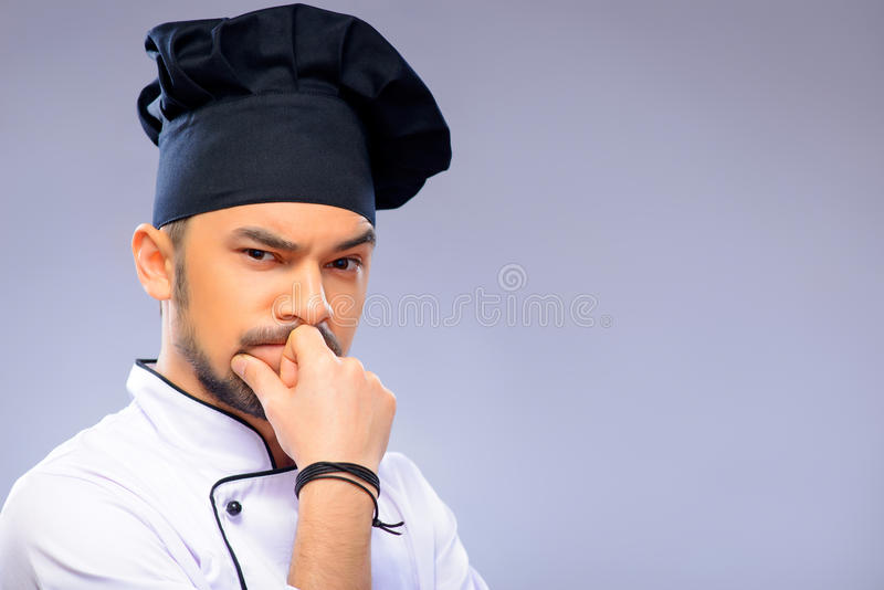 Portrait of young handsome cook. Deep in thoughts. Portrait of serious handsome cook keeping his hand on his chin and looking at camera while standing against royalty free stock image