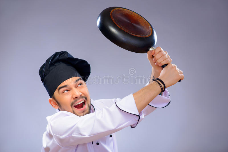 Portrait of young handsome cook. Loosing his temper. Closeup portrait of handsome angry cook striking somebody with his frying pan while standing over grey royalty free stock photography