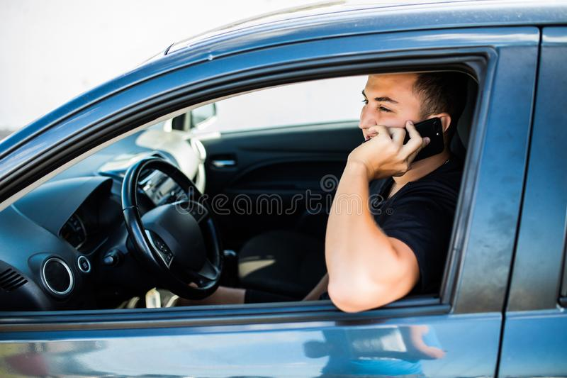 Portrait of young handsome man driving car and speaking on mobile phone. stock photography