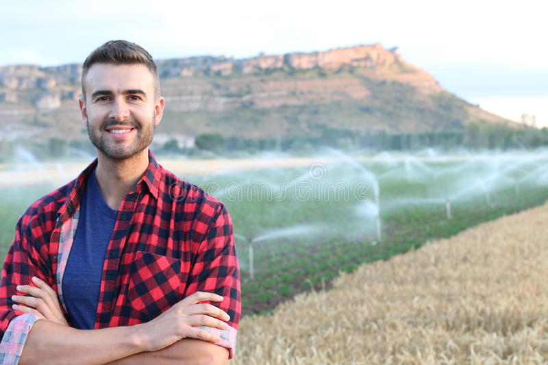 Portrait of young handsome farmer smiling on farmland stock photo