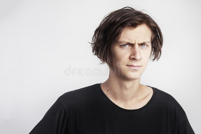 Portrait of young handsome hipster man look serious stressful, black t-shirt, white background royalty free stock photography