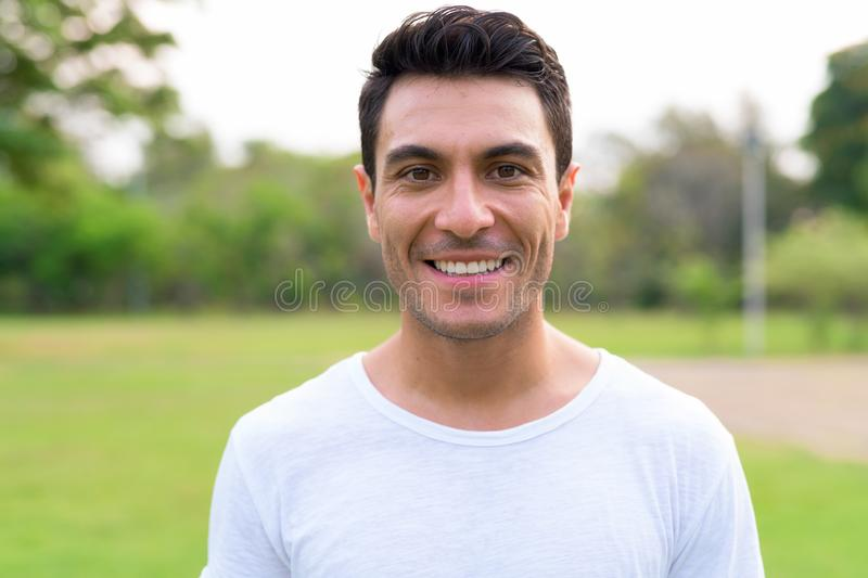 Face of happy young handsome Hispanic man smiling at the park. Portrait of young handsome Hispanic man in the park outdoors royalty free stock photos