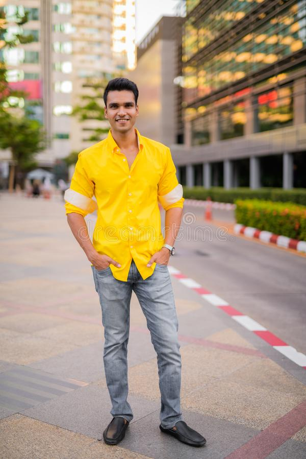 Full body shot of happy young handsome Indian man smiling in the city street. Portrait of young handsome Indian man in the city streets outdoors stock photography