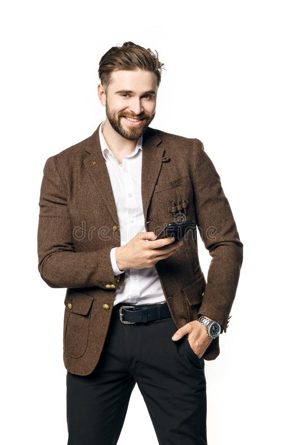 A portrait of a young handsome male businessman with a beard is smiling arms crossed and holds the phone. stock image