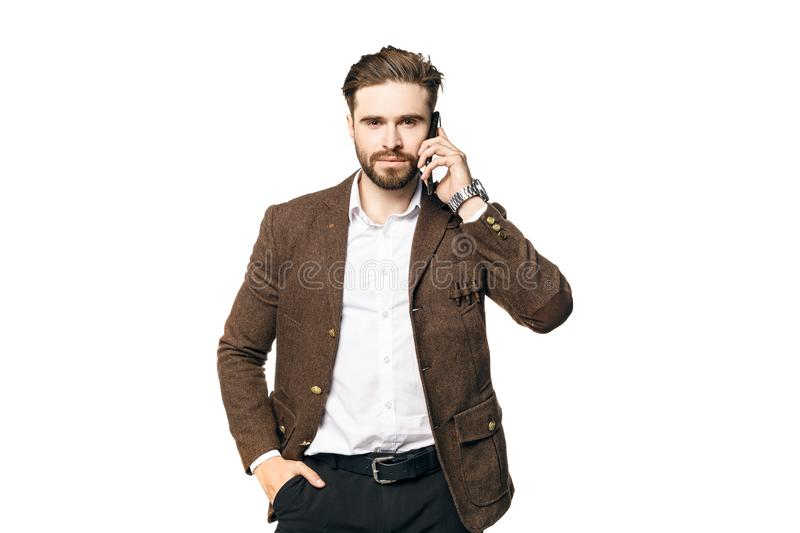 A portrait of a young handsome male businessman with a beard who is  seriously talking on the phone. stock photo