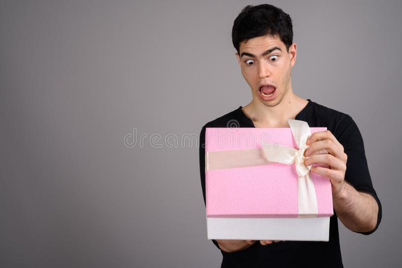 Portrait of young handsome man against gray background. Studio shot of young handsome man holding gift box against gray background royalty free stock photo