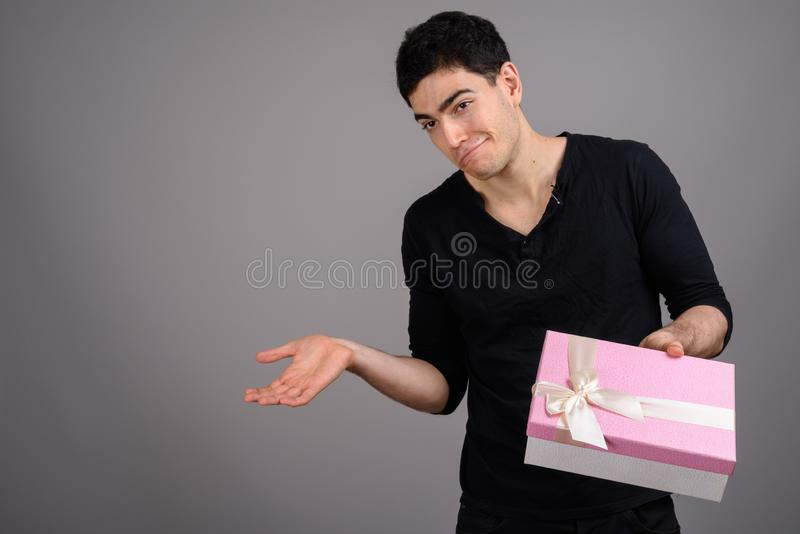 Portrait of young handsome man against gray background. Studio shot of young handsome man holding gift box against gray background stock photo