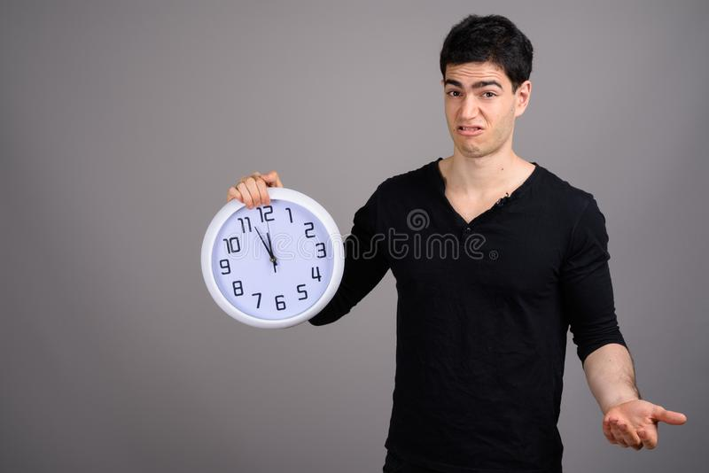 Portrait of young handsome man against gray background. Studio shot of young handsome man holding wall clock against gray background royalty free stock photography
