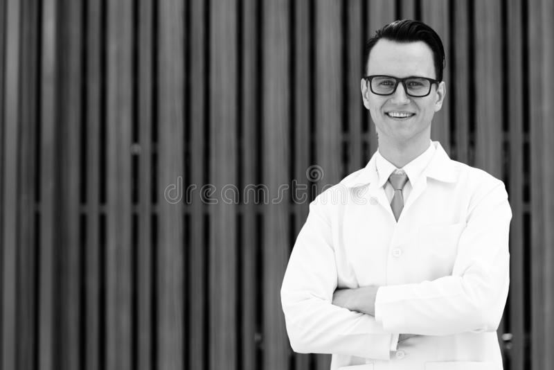 Portrait of young happy man doctor smiling with arms crossed outdoors stock photography