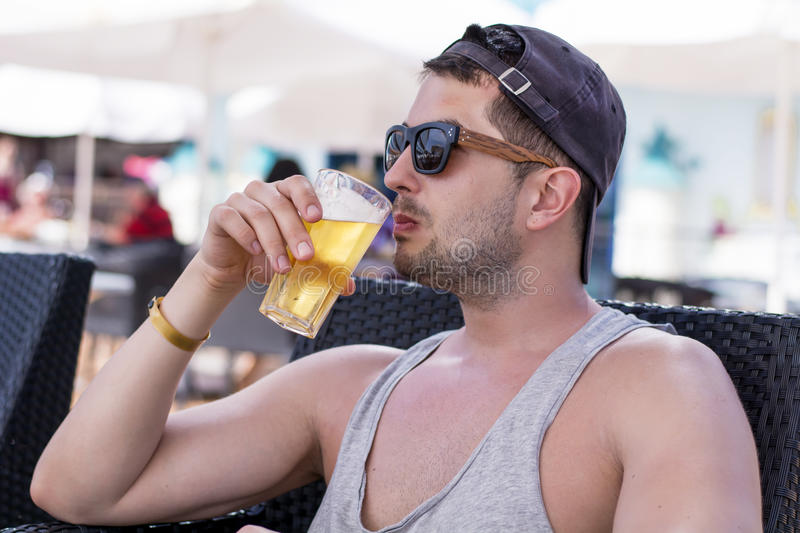 Portrait of young handsome man drinking cold refreshing beer. Outdoor stock photography