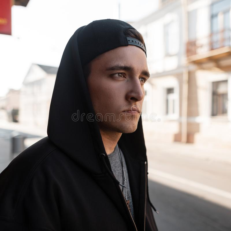 Portrait of a young handsome man in fashionable black clothes with a hood in a stylish cap near a vintage building on the street. On a sunny summer day royalty free stock photos