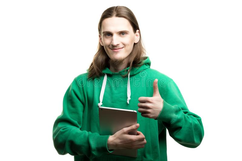 Portrait of a young handsome man in green hoodie looking at the camera, holding a digital tablet in one hand and showing okay gest royalty free stock image