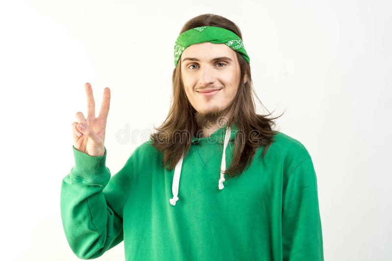 Portrait of young handsome man in green hoodie with a peaceful smile, looking into camera and showing peace sign stock image