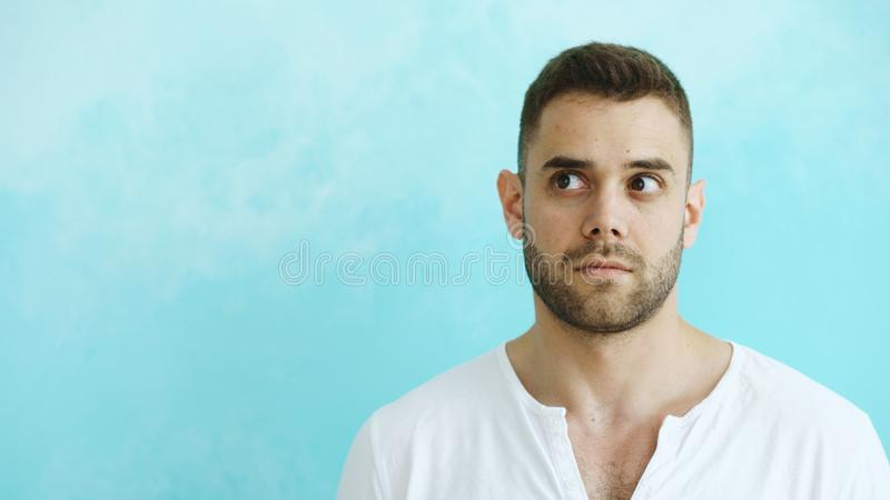 Portrait of young handsome man grimacing into camera and show different emotions on blue background stock image