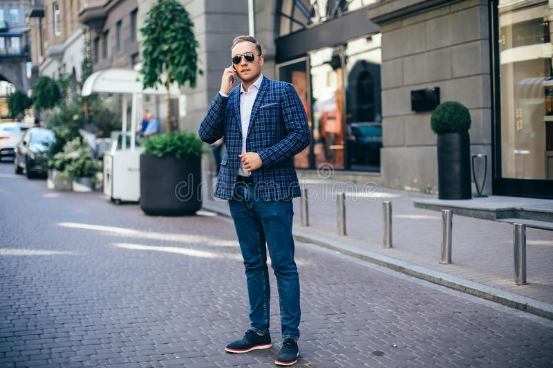 Portrait of a young handsome man, model of fashion, wearing tinted sunglasses in urban background royalty free stock photos