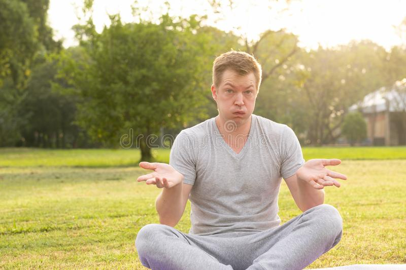 Young frustrated man shrugging shoulders at the park. Portrait of young handsome man relaxing at the park royalty free stock image