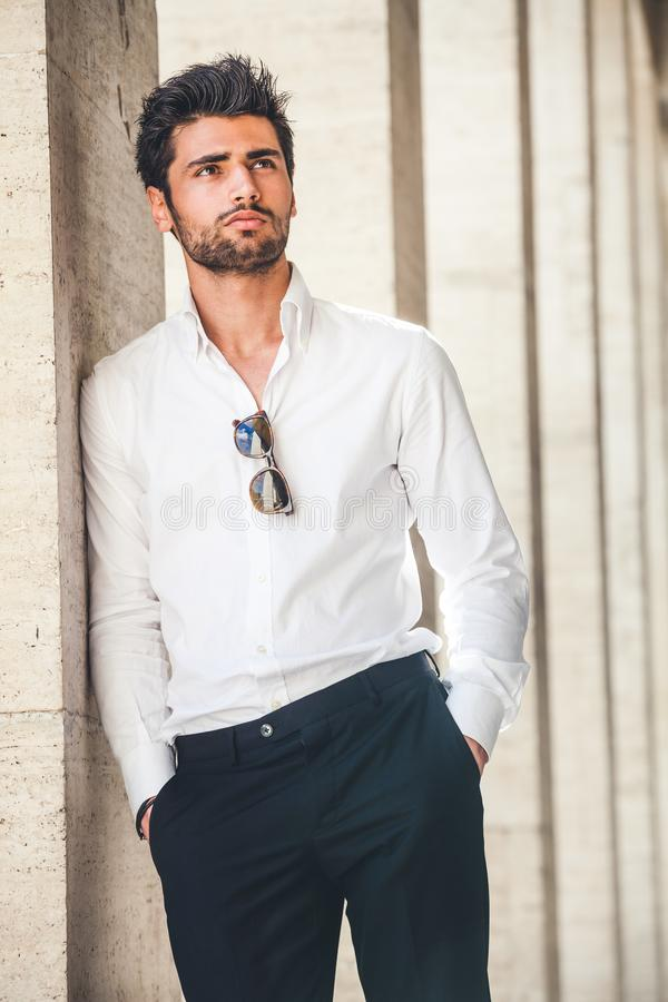 Portrait of young handsome man in white shirt outdoor. stock photos