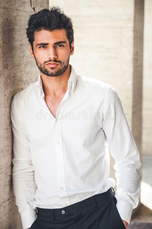Portrait of young handsome man in white shirt outdoor. Nice appearance with stylish hair and beard. Leaning with a side on a wall royalty free stock photos