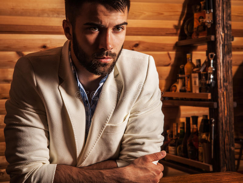 Portrait of young handsome man in white suit near home bar. royalty free stock images