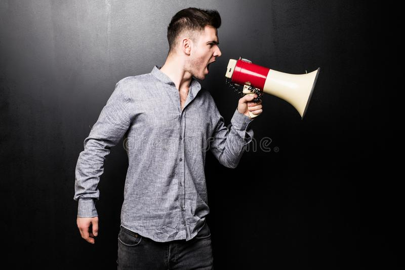 Portrait of young handsome man yelling into the megaphone over black background royalty free stock photos