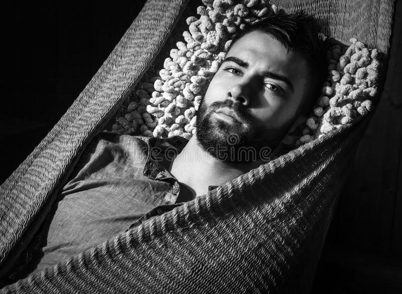 Portrait of young handsome serious man in a hammock. Black-white close-up photo. royalty free stock images