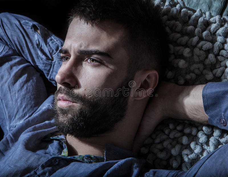 Portrait of young handsome serious man in a hammock. stock photos