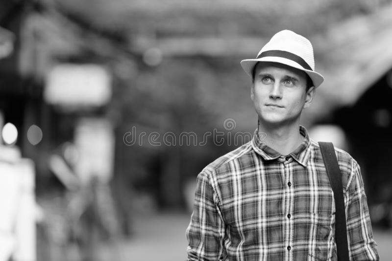 Young handsome tourist man looking up while travelling in the streets outdoors stock photo
